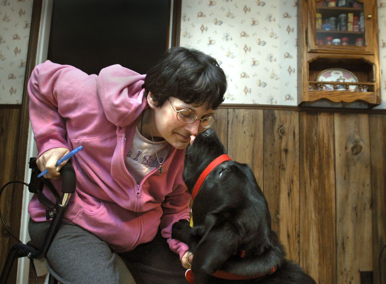 MS-patiente Tami Hernandez knuffelt haar helpende hond, die voor haar een onmisbare hulp in het dagelijks leven is. Foto AP ** ADVANCE FOR WEEKEND EDITIONS OF JAN. 7-8 ** Tami Hernandez gets a kiss from her dog, Cole, in Canaan, N.H., on Dec. 29, 2005. Cole, an assistance dog, helps Hernandez, who has multiple sclerosis, with her daily routines. Cole joined Hernandez? family this summer.(AP PhotoVAlley News, Jennifer Hauck)
