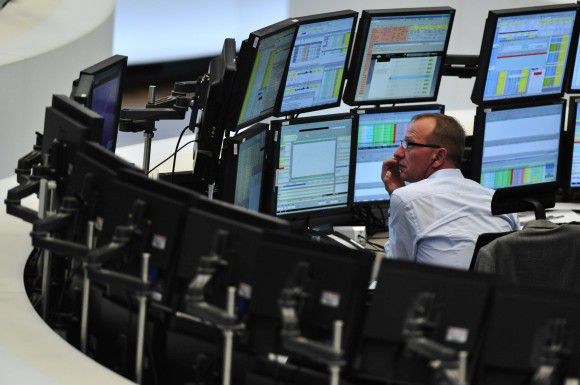 A trader sits in front of screens showing the German DAX index in Frankfurt am Main on October 27, 2011 at the German Stock Exchange. German stocks opened sharply higher today after EU leaders sealed a deal to contain the eurozone debt crisis at a summit in Brussels. AFP PHOTO / MARC TIRL +++ GERMANY OUT
