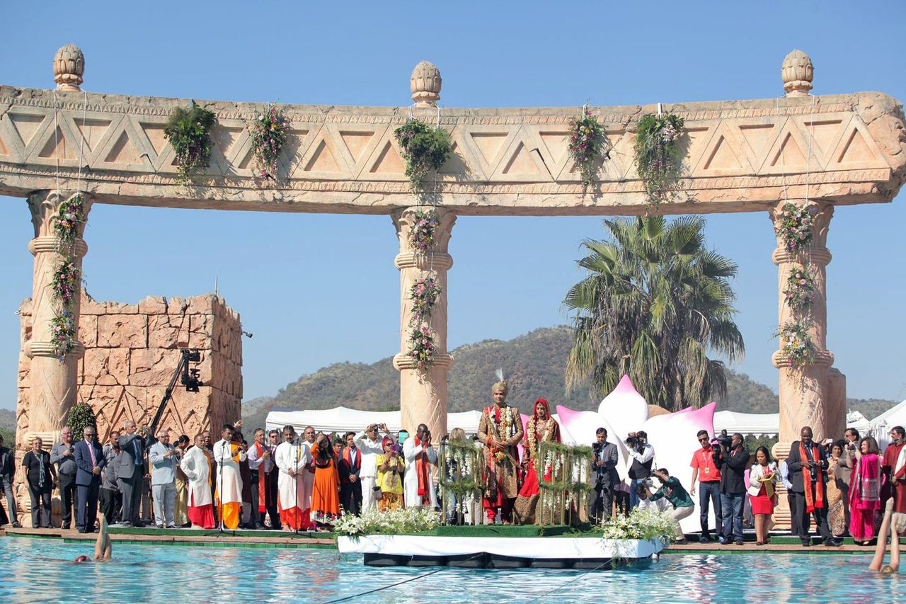 """This picture courtesy of the Gupta family shows Vela Gupta and her husband Indian-born Aaskash Jahajgarhia posing with relatives and guests during ceremonies for their wedding in Sun City, South Africa, on May 1, 2013. South Africa's government announced the suspension of a slew of officials and military personnel on May 3, 2013 as it tried to limit the political and diplomatic fallout from a lavish Indian wedding. A gaggle of top ministers appeared in public to explain how a rich Indian family with ties to President Jacob Zuma landed a Airbus A330 laden with wedding guests at a military base without permits. RESTRICTED TO EDITORIAL USE -- MANDATORY CREDIT """"AFP PHOTO / COURTESY OF THE GUPTA FAMILY"""" -- NO MARKETING OR ADVERTISING CAMPAIGNS -- DISTRIBUTED AS A SERVICE TO CLIENTS"""
