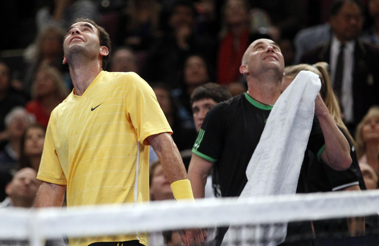 Tennis legends Pete Sampras (L) and Andre Agassi look up at a monitor playing highlights of one of their U.S. Open Final matches during their exhibition match at the BNP Paribas Showdown at Madison Square Garden in New York February 28, 2011. REUTERS/Mike Segar (UNITED STATES - Tags: SPORT TENNIS)