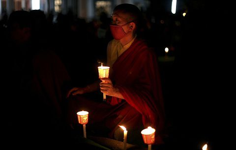 A Tibetan Buddhist monk holds a candle during a candlelit vigil for Tibetans who self-immolated in Tibet, in Bodh Gaya, Bihar state, India, Sunday, Jan. 8, 2012 . Bodh Gaya is believed to be the place where Buddha attained enlightenment. (AP Photo/Altaf Qadri)