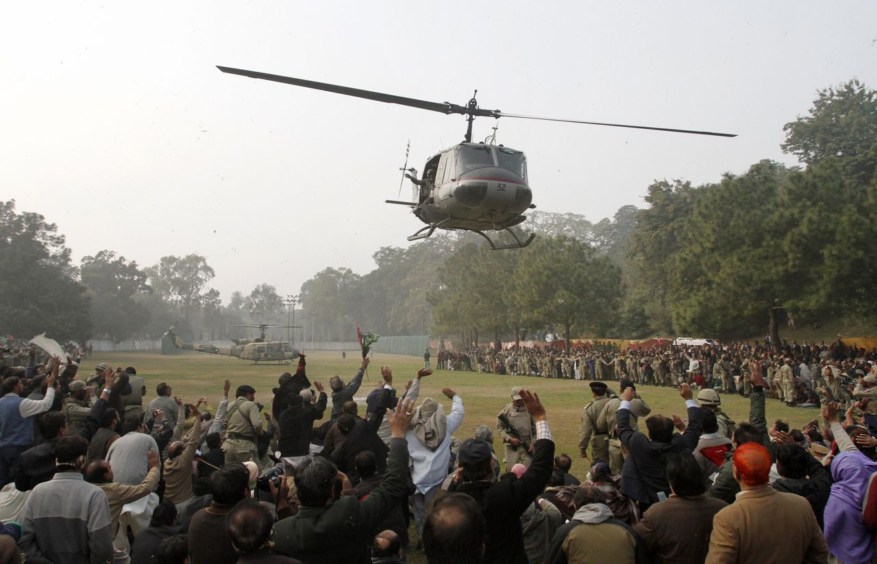 Supporters wave at a helicopter carrying the body of Punjab Governor Salman Taseer as it takes-off from the grounds of the Governor's House, where thousands took part in Taseer's funeral prayers, in Lahore January 5, 2011. Five hundred moderate Pakistani religious scholars have warned that anyone who expresses grief over the assassination of a senior ruling party official who opposed the country's blasphemy law could suffer the same fate. The Punjab province governor was killed on Tuesday by one of his guards, who was apparently incensed by the politician's opposition to the blasphemy law, in a parking lot at a block of shops popular with foreigners in Islamabad. REUTERS/Mohsin Raza (PAKISTAN - Tags: OBITUARY CRIME LAW CIVIL UNREST)