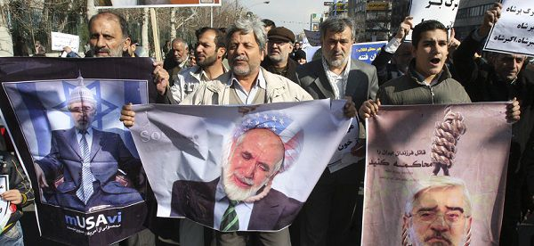 ". Some thousands of pro-government demonstrators walked through the streets calling for the execution of two opposition leaders, Mir Hossein Mousavi and Mahdi Karroubi, in response to anti-government protests earlier this week. Writing on banner at left in Farsi reads ""a product from USA and Zionist"". (AP Photo/Vahid Salemi"