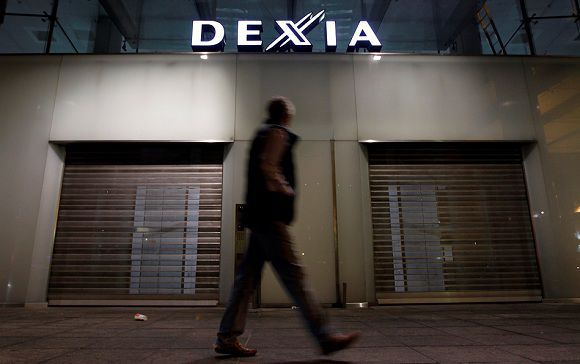 Caption: A man walks past the closed entrance of the Belgian-French financial services group Dexia's headquarters in Brussels October 9, 2011. France, Belgium and Luxembourg agreed to a rescue plan for Dexia SA on Sunday ahead of a planned board meeting expected to decide on a break-up of the first lender to fall victim to the euro zone crisis. REUTERS/Francois Lenoir (BELGIUM - Tags: BUSINESS POLITICS)