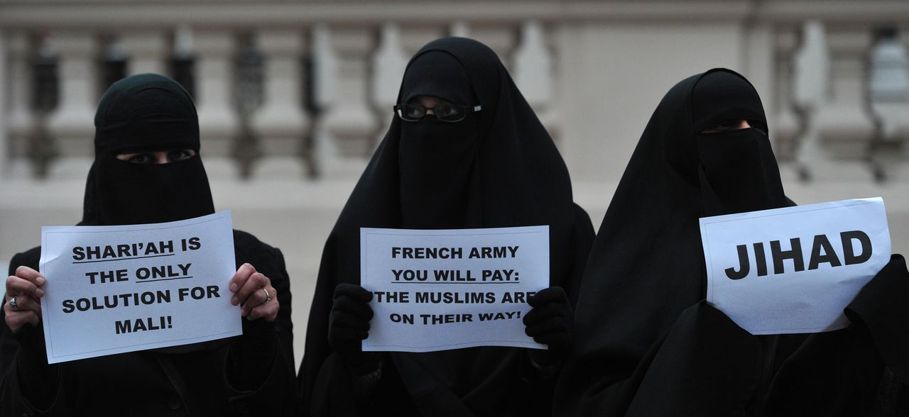 Veiled Muslim women hold up signs as they join a protest in response to French military action in Mali outside the French embassy in central London on January 12, 2013. Around 50 Muslim protesters shouted slogans and waved signs as they demonstrated outside the French embassy against French intervention in Mali. France sent troops on January 11 to help Malian forces hold back a rebel advance towards the capital Bamako, and on January 12 Paris announced that a French military pilot had been killed. AFP PHOTO / CARL COURT