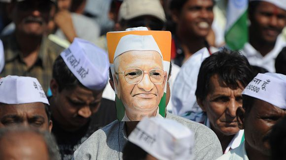 A supporter of Indian activist Anna Hazare wears a mask on the first day of Hazare's 3 day-long fast in Mumbai on December 27, 2011. The 74-year-old former soldier, Hazare, along with volunteers of his India Against Corruption (IAC) organisation embarks on a fresh hunger strike against a proposed new law to tackle endemic graft. At least 40,000 people a day are expected to attend the three-day fast in the city's northern suburbs, organisers said, even though lawmakers are still debating the planned legislation in parliament. The former army driver's latest high-profile protest comes amid question marks over the integrity of his anti-corruption movement, as well as criticism that he is riding roughshod over the democratic process. AFP PHOTO/ Indranil MUKHERJEE