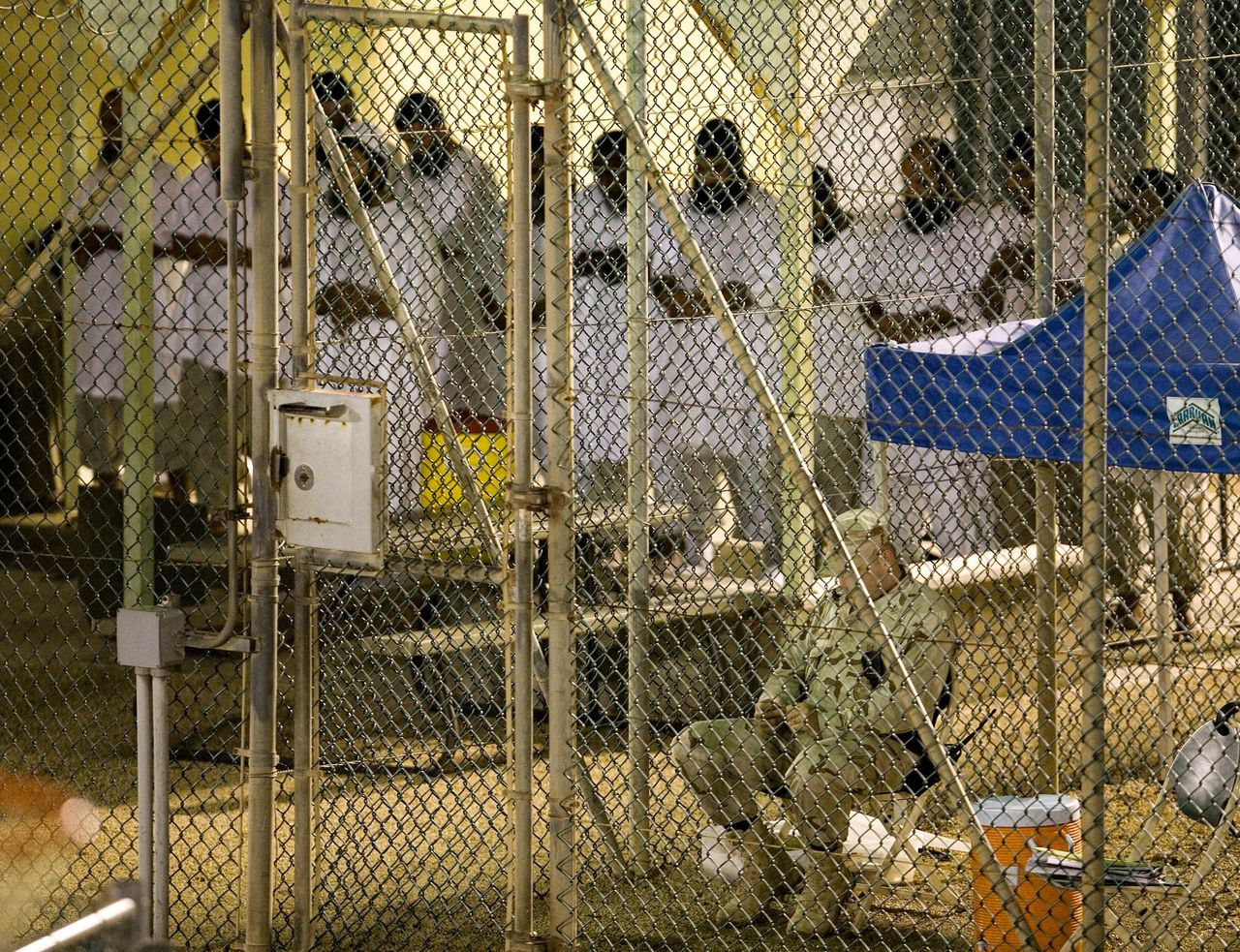 Ochtendgebed in het Amerikaanse detentiekamp Guantánamo Bay. De Amerikaanse minister van Justitie wil CIA-medewerkers vervolgen die te ver zijn gegaan bij het verhoren van terreurverdachten. Foto Reuters In this image reviewed by the U.S. Military, a group of Guantanamo detainees participate in the early morning Islamic prayer, as a U.S. military guard sits nearby at Camp 4 detention facility at the U.S. Naval Base, in Guantanamo Bay, Cuba, Tuesday, Nov. 18, 2008. A federal judge on Thursday, Nov. 20 ordered the release of five Algerians held at Guantanamo Bay, Cuba, and the continued detention of a sixth in what is being called a blow to the Bush administration's policy to keep terror suspects locked up without charges. (AP Photo/Brennan Linsley)