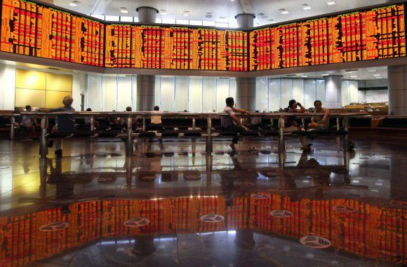 Malaysia stockbrokers sit under the digital share price board showing the Malaysian Index in Kuala Lumpur on August 8, 2011. Standard & Poor's on August 8 said its US credit rating downgrade will have no immediate impact on Asia-Pacific sovereign ratings, but could have negative consequences longer-term. AFP PHOTO / Mohd Rasfan