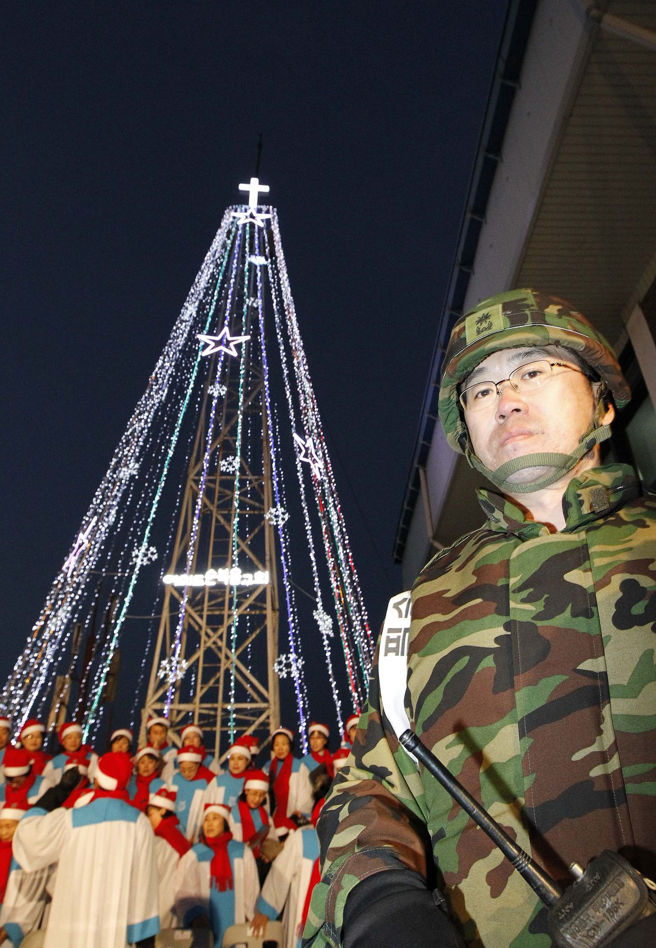 "(FILES) A South Korean military officer stands guard as Christians prepare a lighting ceremony in front of a Christmas tree atop a military-controlled hill near the tense land border in Gimpo, west of Seoul, on December 21, 2010. North Korea warned South Korea on December 11, 2011 of ""unexpected consequences"" if Seoul displays Christmas lights near the tense border, and vowed to retaliate for what it called propaganda attempts. AFP PHOTO / KIM JAE-MYUNG / FILES"