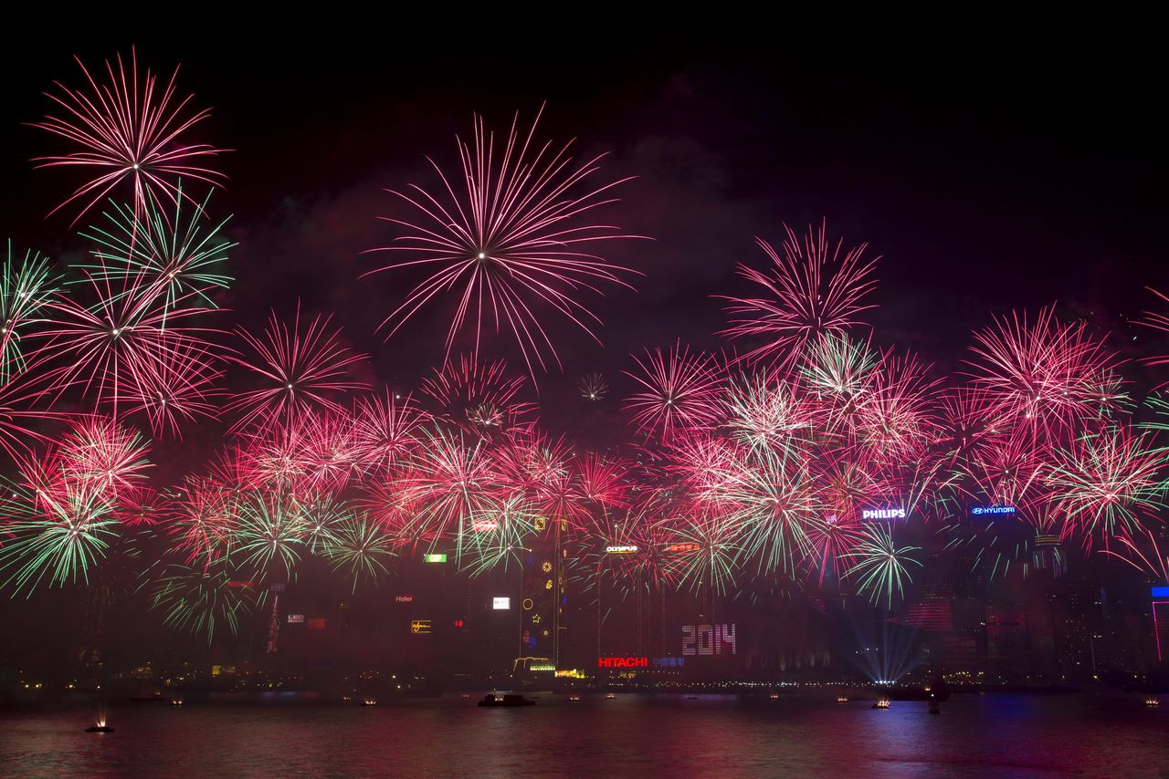 epa04004567 Fireworks explode over the Victoria Harbour to celebrate New Year in Hong Kong, China, 01 January, 2014. Hong Kong Police said up to 350,000 spectators were expected to fill the streets for the city's countdown events with Victoria Harbour as the main focus for new year celebrations. EPA/JEROME FAVRE