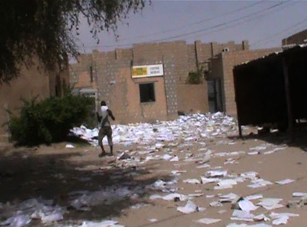 ATTENTION FRENCH CLIENTS - EMBARGOED, RELEASABLE IN FRANCE ON APRIL 6, 2012 AT 18h30GMT. THIS RESTRICTION APPLIES TO ALL MEDIA, INCLUDING WEBSITES IN FRANCE AND FRENCH OVERSEAS TERRITORIES TV grab shows a man walking among scattered papers outside a rampaged administation building on April 3, 2012 in Timbuktu. Mali's National Movement for the Liberation of Azawad (MNLA) rebels declared independence on April 6, 2012 in the north, splitting the coup-wracked country in two, as warnings rang out of a humanitarian disaster in what was once considered Africa's democratic success story. MNLA, captured northern Mali with Islamist groups over the past two weeks following a coup in the capital. AFP PHOTO / AFPTV / FRANCE 2