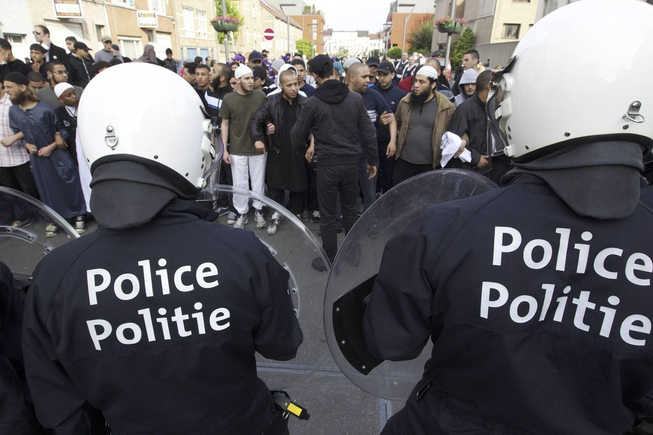 Police officers stand guard in front of a crowd of Muslim protesters in Sint-Jans-Molenbeek (Molenbeek-Saint-Jean), in Brussels, on June 1, 2012. On May 31 small riots broke out in Molenbeek, after a woman in niqab (veil that completely covers the face) was checked by two police officers and asked to take off her full veil, which has been illegal in Belgium for over a year. The woman was brought to a police station after her refusal to comply and she allegedly assaulted two female police officers once there, leading to tensions in the local community. AFP PHOTO / BELGA / NICOLAS MAETERLINCK ***Belgium Out***