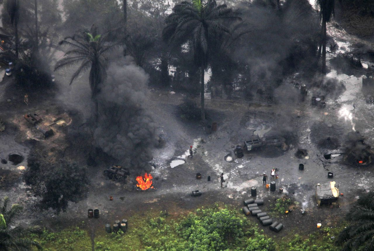 Smoke rises from an illegal crude oil refinery site in an Ogoni community in Nigeria's Niger Delta July 7, 2010. REUTERS/Akintunde Akinleye (NIGERIA - Tags: CRIME LAW ENVIRONMENT ENERGY BUSINESS)