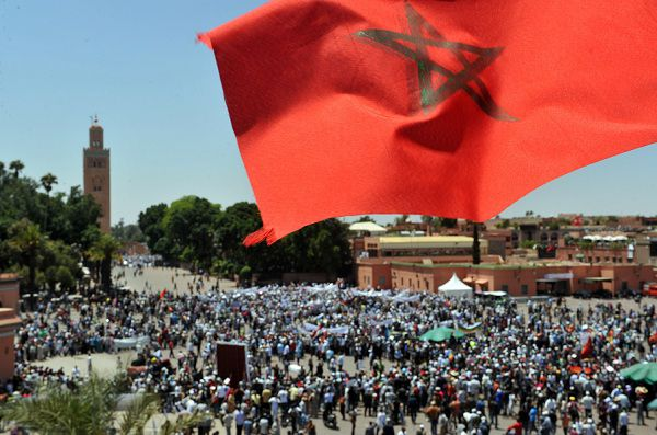 Caption: The national flag of Morocco flies as people gather for a demonstration by the 20th February movement in Marrakesh on May 8, 2011 to denounce terrorism following last month's deadly bomb attack at a the Argana cafe in Djemaa El Fna square and to call for democratic reform. Several thousand demonstrators joined the march which was the second such protest in two days. AFP PHOTO /ABDELHAK SENNA