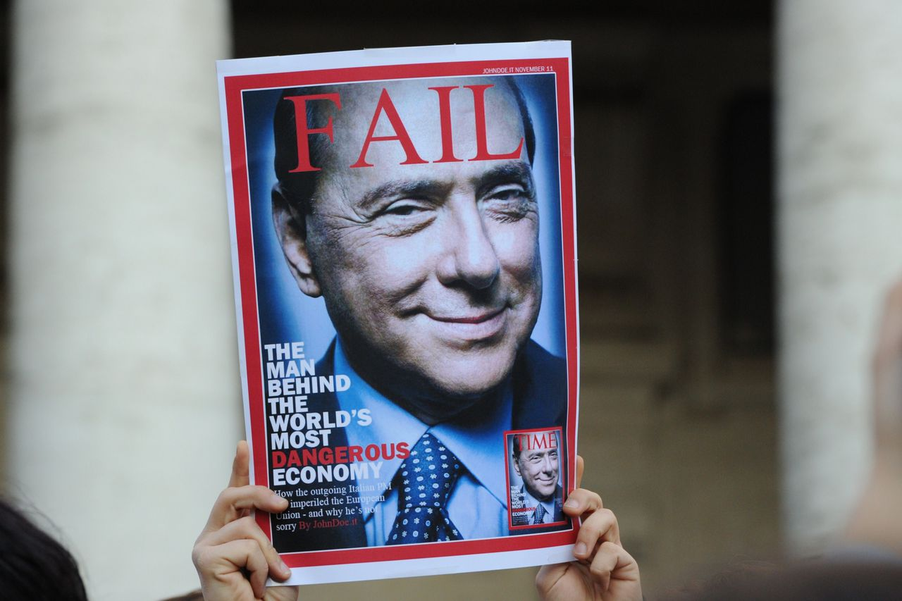 "A man holds a fake copy of ""Time"" magazine called ""Fail"" and showing Italy's Prime Minister Silvio Berlusconi outside Palazzo Chigi, Italy's Prime Ministry on November 12, 2011 in Rome. Italian Prime Minister Silvio Berlusconi was set to resign the same day after a parliamentary revolt and a wave of market panic that has shaken the eurozone, leaving behind an uncertain political future. AFP PHOTO / GABRIEL BOUYS"