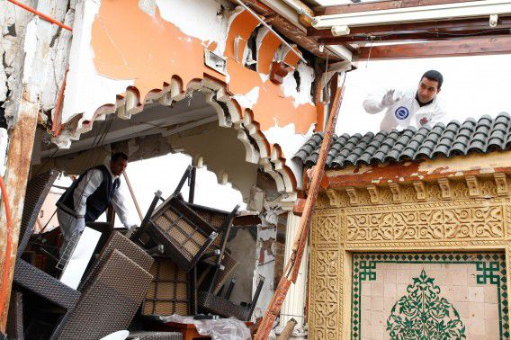 FILE - In this Saturday, April, 30, 2011 file photo, police inspect the debris at the Argana cafe where a bomb was detonated Thursday, April 28, 2011 in Marrakech, Morocco. Moroccan authorities have pinned this deadly attack on Adel al-Othmani, who was inspired by al-Qaida and tried unsuccessfully for years to join the international terror network before returning to Morocco to devise an attack of his own. (AP Photo/Abdeljalil Bounhar, File)