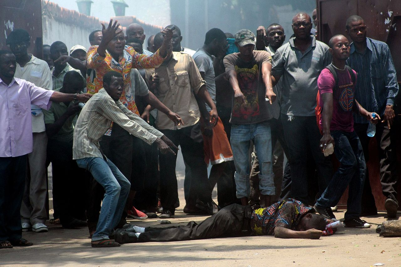 "Supporters of Democratic Republic of Congo's ""Union for Democracy and Social Progress"" (UDPS) party stand around a fellow injured protestor outside the party's headquarters in Kinshasa, on October 6, 2011. Protesters and police were injured and at least eight protesters were arrested after police dispersed protestors who had gathered for a demonstration march demanding more transparency in the November 28 election preparation process. On September 27 another ""peaceful"" march by supporters of the opposition had been rapidly dispersed by police. AFP PHOTO / DIDI-JUNIOR KANNAH"