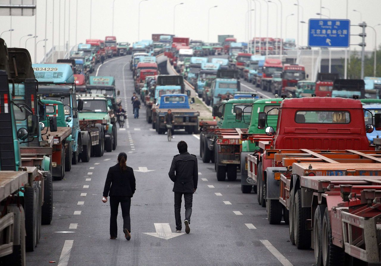 People walk along an unfinished road being used by truck drivers to park their container trucks near a port in Shanghai April 21, 2011, following a protest nearby the area earlier in the morning. Truck drivers were planning a second protest in the afternoon only to be dispersed by the police. Container truck drivers protested on Wednesday and Thursday in Shanghai over rising costs and surcharges, drivers and bystanders said. REUTERS/Carlos Barria (CHINA - Tags: CIVIL UNREST BUSINESS IMAGES OF THE DAY)