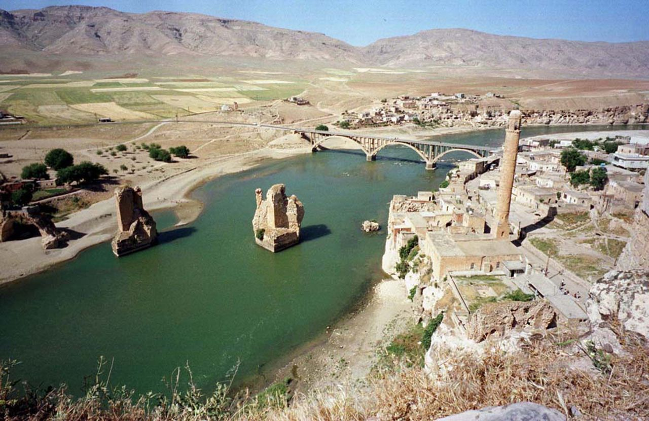 Het eeuwenoude dorp Hasankeyf aan de Tigris, ooit een bloeiende stad in Mesopotamië, dreigt onder water te verdwijnen door de bouw van een grote stuwdam. Foto Reuters The Tigris river flows through the once-powerful town of Hasankeyf which it has sustained through wars and hardship for thousands of years. Early in the next millennium those same clear waters will rise up to submerge the crumbling ruins and caves for ever. All will be resettled for the sake of a huge energy and irrigation scheme to regenerate Turkey's backward southeast. Picture was taken on 19MAY99. FS/FMS