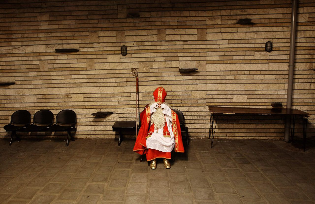 A man dressed as Saint Nicolas waits for children at a scout company in Brussels December 4, 2011. In Belgium, children traditionally wait for Saint Nicolas to bring them sweets and presents on the night of December 5. REUTERS/Yves Herman (BELGIUM - Tags: SOCIETY RELIGION TPX IMAGES OF THE DAY)