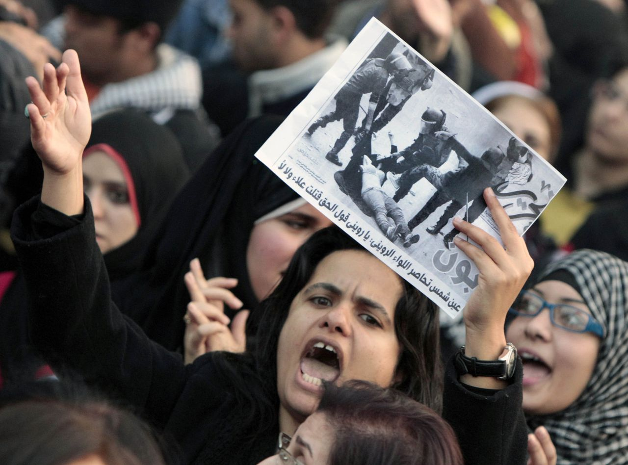 """An Egyptian woman raises a copy of Al Tahrir newspaper fronted by a picture showing half naked woman protester beaten by army soldiers as hundreds of Egyptian women march at Cairo streets angered by the recent violence used against them during clashes between police and protesters in Cairo, Egypt Tuesday, Dec. 20, 2011. Egypt's ruling generals are coming under mounting criticism at home and abroad for the military's use of excessive force against unarmed protesters, including women, as they try to crush the pro-democracy movement calling for their ouster. Arabic read """" Ein Shams surround the military council"""". (AP Photo/Amr Nabil)"""
