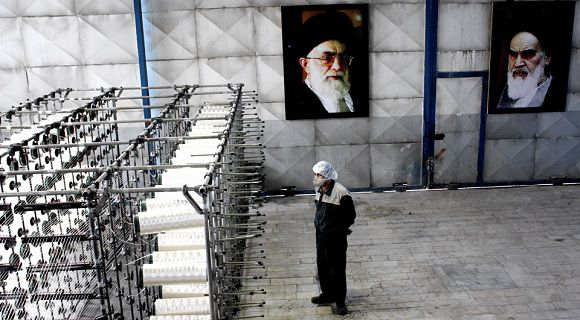 Caption: An Iranian worker stands under portraits of late Iranian revolutionary founder Ayatollah Khomeini, right, and supreme leader Ayatollah Ali Khamenei, beside a production line of a carbon fiber factory of the Defense Ministry, in Tehran, Iran, Saturday, Aug. 27, 2011. Iran has inaugurated its own production of carbon fiber, a material under U.N. embargo because of its potential use in the country's controversial nuclear program, the official IRNA news agency reported Saturday. (AP Photo/ISNA, Abdolvahed Mirzazadeh)