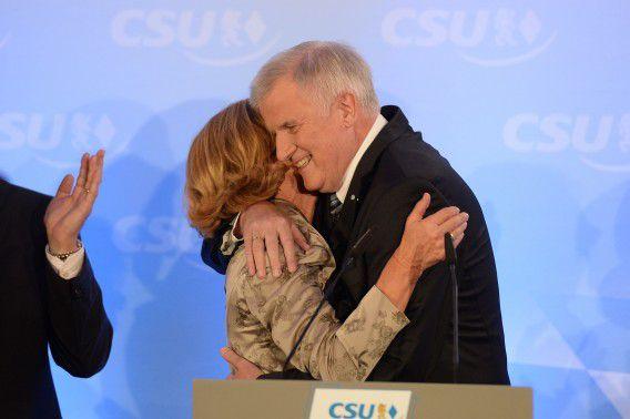 Deelstaatsleider Horst Seehofer (rechts) wordt door zijn vrouw Karin gefeliciteerd met de overwinning van zijn CSU, de zusterpartij van bondskanselier Merkels CDU.