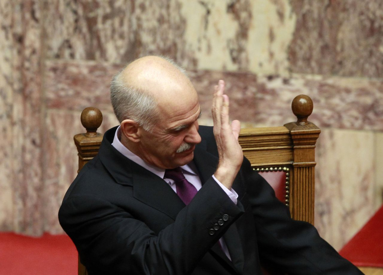 "Greek Prime Minister George Papandreou raises his hand to vote ""yes"" as Greek lawmakers approved in principle an austerity law cutting wages and hiking taxes during a parliament session in Athens October 19, 2011. Greek unions began a 48-hour general strike on Wednesday, the biggest protest in recent years. REUTERS/John Kolesidis (GREECE - Tags: POLITICS BUSINESS)"