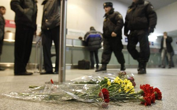 Police officers walk past flowers left on a floor in memory of those killed in Monday's blast at Moscow's Domodedovo airport January 25, 2011. A suspected suicide bomber has struck at Russia's busiest airport, killing at least 35 people and challenging Kremlin efforts to crush armed insurgency and tackle growing nationalist tensions in the country's heartland. REUTERS/Tatyana Makeyeva (RUSSIA - Tags: CRIME LAW TRANSPORT)