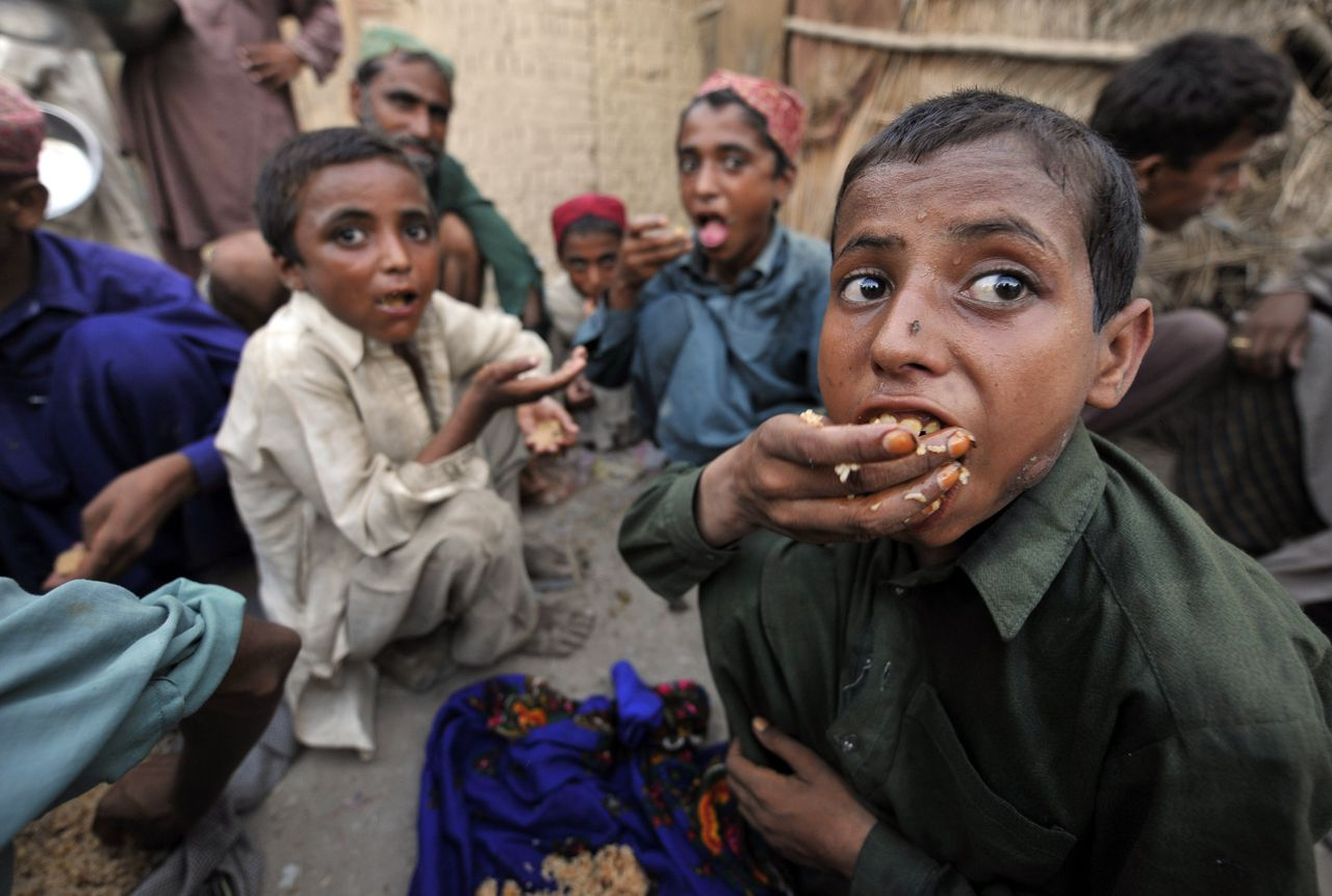 """Pakistani flood survivors eat charity food near a makeshift camp in Sukkur on August 13, 2010. Struggling aid agencies have urged donor nations to rush through 460 million dollars in aid for Pakistan's devastating floods, warning of a potential """"second wave"""" of deaths due to disease. Pakistan says 15-20 million people face direct or indirect harm from the floods. The United Nations believes 1,600 people have died, while Islamabad has confirmed 1,343 deaths. AFP PHOTO/ AAMIR QURESHI"""