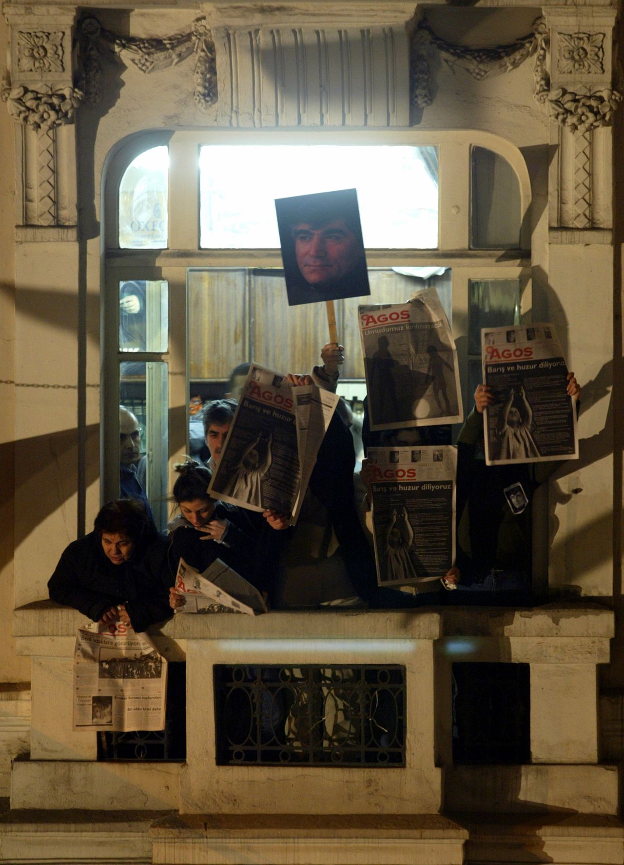 De redactie van Hrant Dinks krant Agos na de moord. Foto AP Employees of the Armenian newspaper Agos display a picture of Hrant Dink and the copies of their newspapers from their office building during a protest Istanbul, Turkey, Friday, Jan. 19, 2007. The murder of Hrant Dink, one of the most prominent voices of Turkey's shrinking Armenian community, sparked protests and international condemnation from Europe, Armenia, the U.S. and numerous media freedom and human rights organizations. Thousands of Turks marched down the street where the journalist, Hrant Dink, was killed. (AP Photo/Osman Orsal)