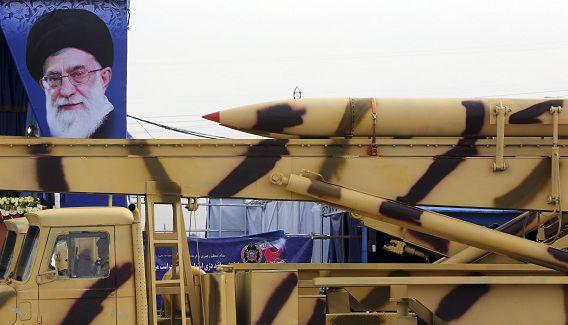 Een raket wordt verplaatst door het Iraanse leger, daarachter een portret van opperste geestelijk leider Ali Khamenei.