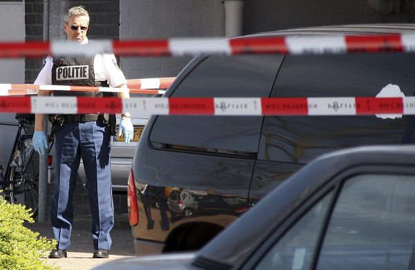 A police officer looks at the scene of a shooting incident at a shopping mall in Alphen aan den Rijn, southern Netherlands April 9, 2011. A gunman's deadly rampage through a shopping mall was met on Sunday with disbelief by residents of the quiet Dutch town who once thought such carnage could not happen in their country. Dressed in camouflage trousers and a bomber jacket, Tristan van der Vlis opened fire with an automatic weapon in a parking lot on Saturday and walked calmly into Ridderhof mall, where he continued shooting. Six people died and 17 were wounded. Picture taken April 9, 2011. REUTERS/Stephan Verwaaij (NETHERLANDS - Tags: CRIME LAW CIVIL UNREST) MANDATORY CREDIT