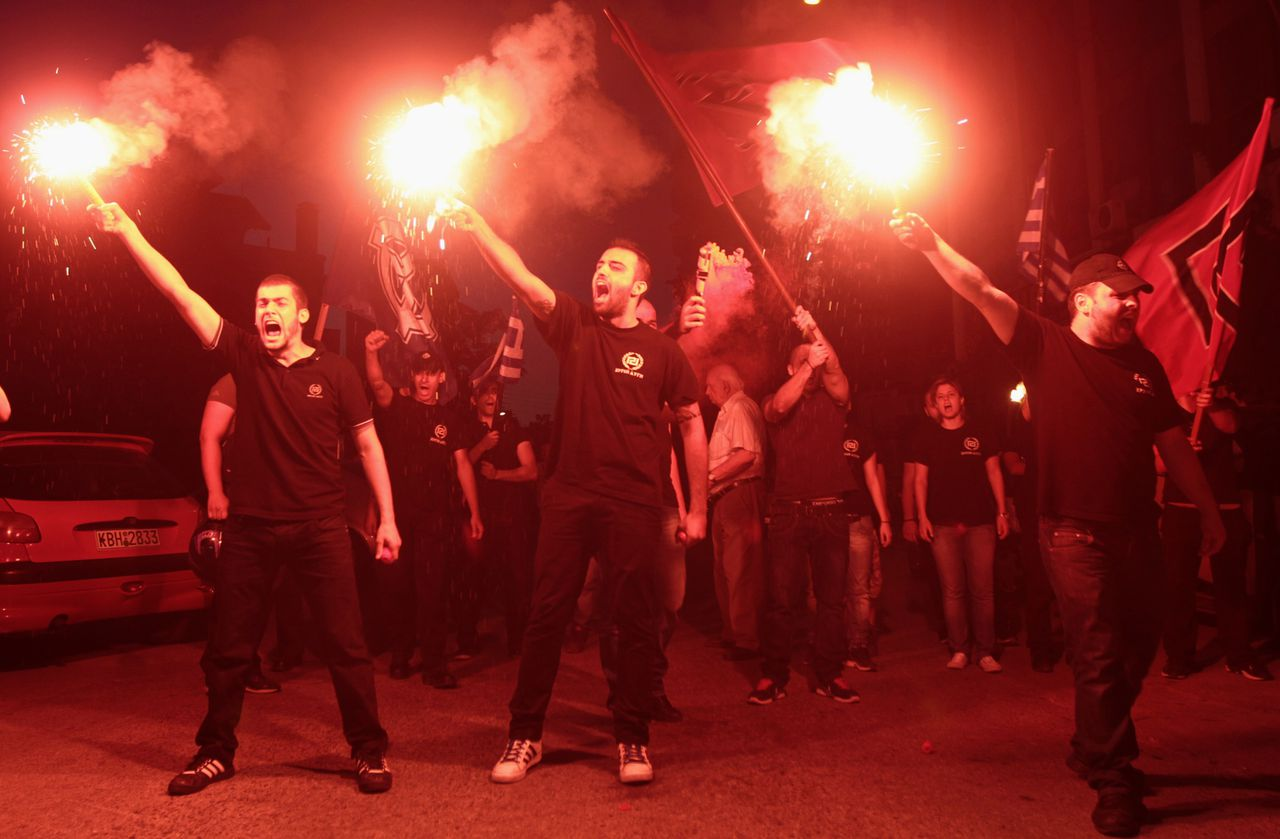 Members of extreme right party Golden Dawn celebrate holding flares in the northern coastal city of Thessaloniki after Greece's general elections June 17, 2012. Parties committed to Greece's bailout were on course to secure a parliamentary majority on Sunday and the radical leftists who had vied for first place conceded defeat in an election that could keep the debt-laden country in the euro zone. REUTERS/Grigoris Siamidis (GREECE - Tags: ELECTIONS POLITICS SOCIETY)