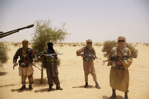 Strijders van de Islamitische groep Ansar Dine tijdens de overrdacht van een gijzelaar in de woestijn buiten Timbuktu, Mali, 24 april.