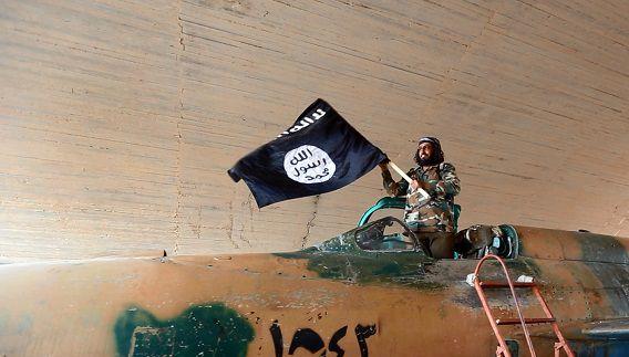 Een foto, verspreid door het 'mediacentrum' van IS in Raqqa, Syrië. Een strijder van de groep houdt een vlag in de lucht vanuit een gevechtsvliegtuig dat werd veroverd op het Syrische leger.