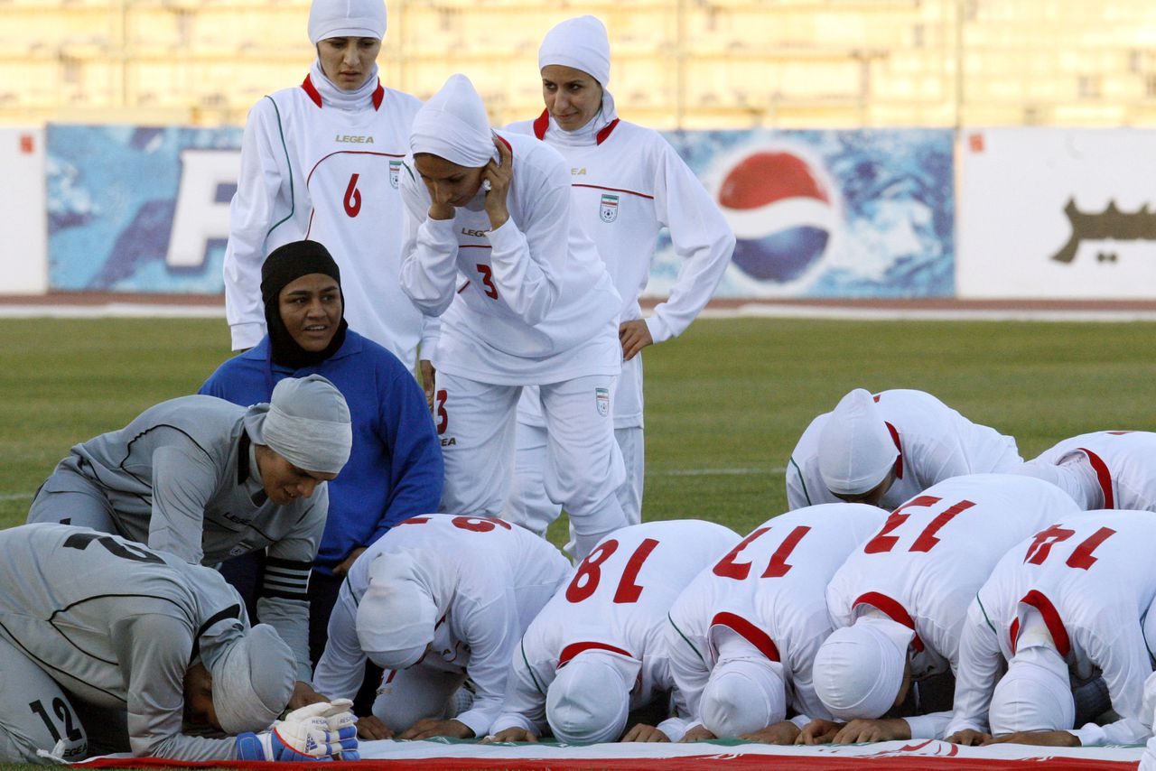 A picture dated June 3, 2011 shows players of the Iranian national women football team kneeling around their national flag in Amman, moments after they were barred from playing an Olympic qualifier against Jordan for wearing the traditional Islamic headscarf. The row over the dress code of Iran's women team has been at the heart of a struggle between FIFA and the Iranian football federation. AFP PHOTO/STR