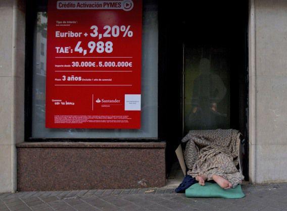 Een dakloze slaapt in het portiek van een bank. Deze week gaf Spanje voor het eerst openlijk aan financiële hulp te willen.