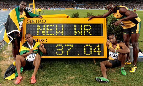 Caption: Jamaica's Usain Bolt, right top, Yohan Blake, right bottom, Nest Carter, left top, and Michael Frater pose with the socreboard, setting a new world record in the Men's 4x100m relay final at the World Athletics Championships in Daegu, South Korea, Sunday, Sept. 4, 2011. Jamaican team won the gold. (AP Photo/David J. Phillip)