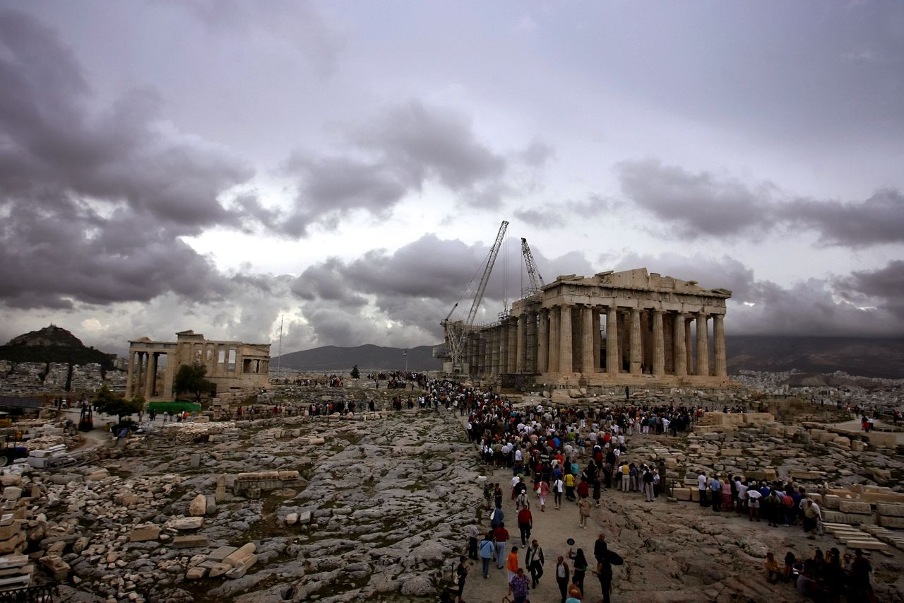 "Toeristen wandelen naar de Parthenon-tempel, bovenop de Acropolis in Athene. Foto AFP (FILES) -- File picture dated 28 September 2007 shows groups of tourists walking to the fifth century BC Parthenon temple, at the top of the Athens' Acropolis hill, 28 September 2006. Egypt is fuming over a competition to choose the world's ""new seven wonders,"" deriding it as a marketing stunt that demeans the pyramids of Giza, the only surviving ancient wonder. Among the 21 sites short-listed for the new competition are Petra in Jordan, the Eiffel Tower, the Acropolis in Athens, the Statue of Liberty, the Taj Mahal, the Sydney Opera House and the Great Wall of China. AFP PHOTO/ARIS MESSINIS"