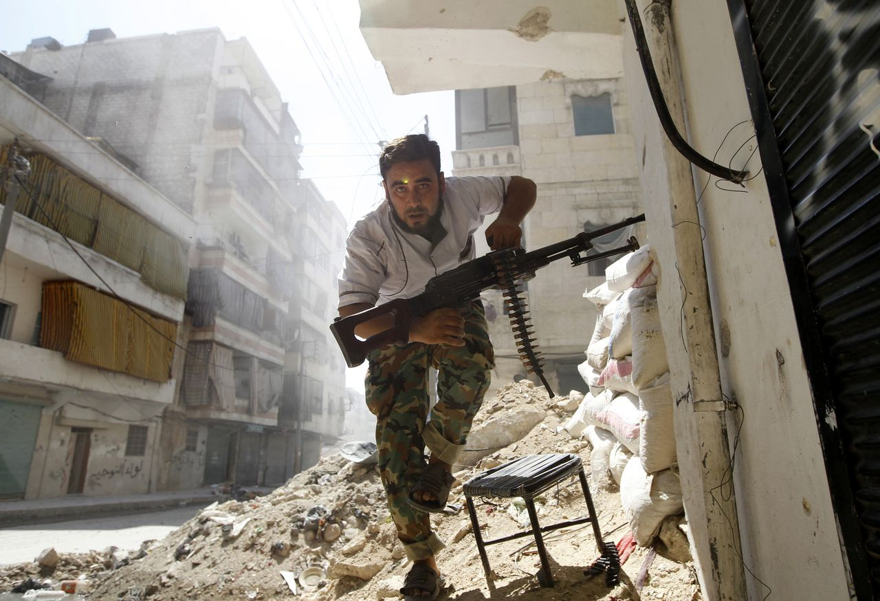 A Free Syrian Army fighter takes cover during clashes with Syrian Army in the Salaheddine neighbourhood of central Aleppo in this August 7, 2012 file photo. This rebel had been firing at the Syrian army when he came under attack from sniper fire, he was pulling back into a secure position when the picture was taken. I was next to him, on the ground, and shooting with a 20mm lens. The yellow dot on his head is a reflection from the camera lens. REUTERS/Goran Tomasevic/Files (SYRIA - Tags: CIVIL UNREST CONFLICT) ATTENTION EDITORS - PICTURE 04 OF 16 FOR PACKAGE 'INSIDE SYRIA WITH THE REBELS'