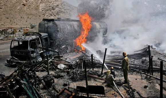 Caption: Firefighters hose down an oil tanker which was set ablaze by gunmen in Quetta June 19, 2011. Gunmen torched the truck carrying fuel for NATO forces in Afghanistan in southwestern Baluchistan province, police said. The driver of the truck was killed in the attack. REUTERS/Naseer Ahmed (PAKISTAN - Tags: CIVIL UNREST IMAGES OF THE DAY)