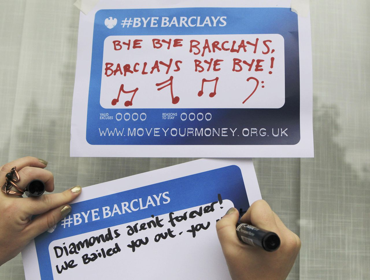 Protestors from the Move Your Money group stick up posters on a branch of Barclays Bank in Westminster central London, July 4, 2012. Barclays chief executive Bob Diamond, who quit this week over an interest rate-rigging scandal, will be questioned by British politicians on Wednesday, when he could drag the Bank of England, the government and rival banks deeper into the Libor interest rate affair. REUTERS/Olivia Harris (BRITAIN - Tags: BUSINESS POLITICS SOCIETY)