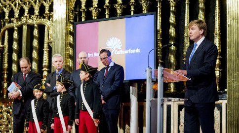 Dik van der Meulen (tweede van links) luistert naar Koning Willem-Alexander na het in ontvangst nemen van de biografieen van de eerste drie Nederlandse koningen.