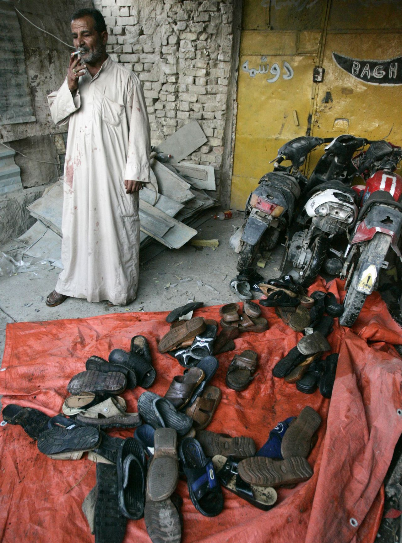Beschadigde schoenen en brommers na aanslag in Bagdad. Foto Reuters A man stands next to footwear and damaged motorcycles after a bomb attack in Baghdad's Sadr city, November 2, 2006. A motorcycle bomb killed seven people and wounded 45 when it exploded in a crowded market, an interior ministry source said. REUTERS/Thaier al-Sudani (IRAQ)