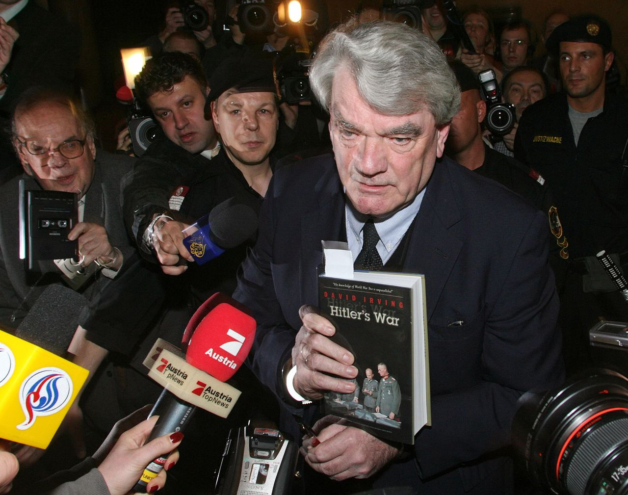 British historian David Irving, facing charges of Holocaust denial in an Austrian court, is handcuffed as he talks to reporters in the courtroom February 20, 2006. Irving, who was arrested when he visited Austria in November to give a speech at a meeting of a right-wing student fraternity, said he had changed his views and he did not question anymore that millions of Jews died in World War Two. REUTERS/Heinz-Peter Bader