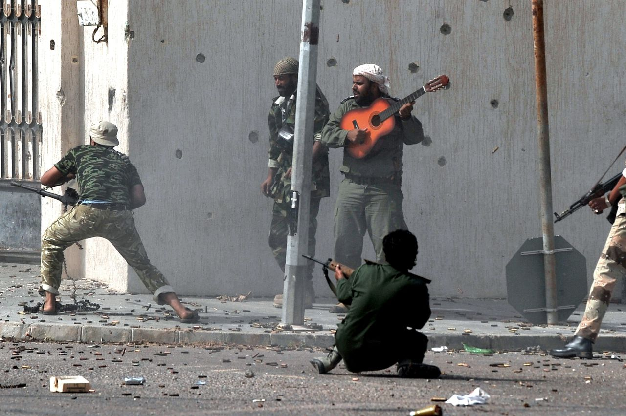 Libya's new regime forces fire their weapons at fighters loyal to fugitive strongman Moamer Kadhafi as a comrade plays a guitar during a battle in Sirte on October 10, 2011, in a drive to control Kadhafi's hometown after a month-long siege. AFP PHOTO / ARIS MESSINIS