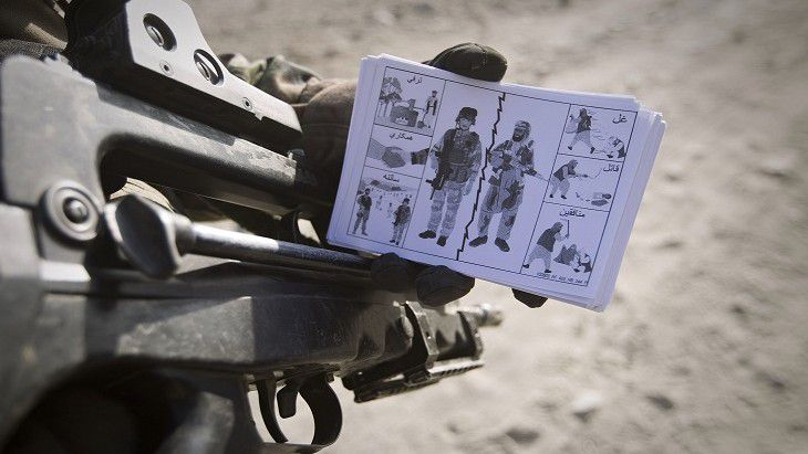"A French soldier from the 7th Mountain Infantry Battalion (7eme bataillon de chasseurs alpins BCA) holds up leaflets to be distributed to local villagers showing the difference between ISAF soldiers and insurgents, during a patrol near Tagab in Kapisa Province on January 25, 2011. France is ""determined"" to keep troops in Afghanistan despite a threat from Al-Qaeda chief Osama Bin Laden linking their mission to the fate of French hostages, the foreign ministry said January 21. AFP PHOTO/Joel SAGET"