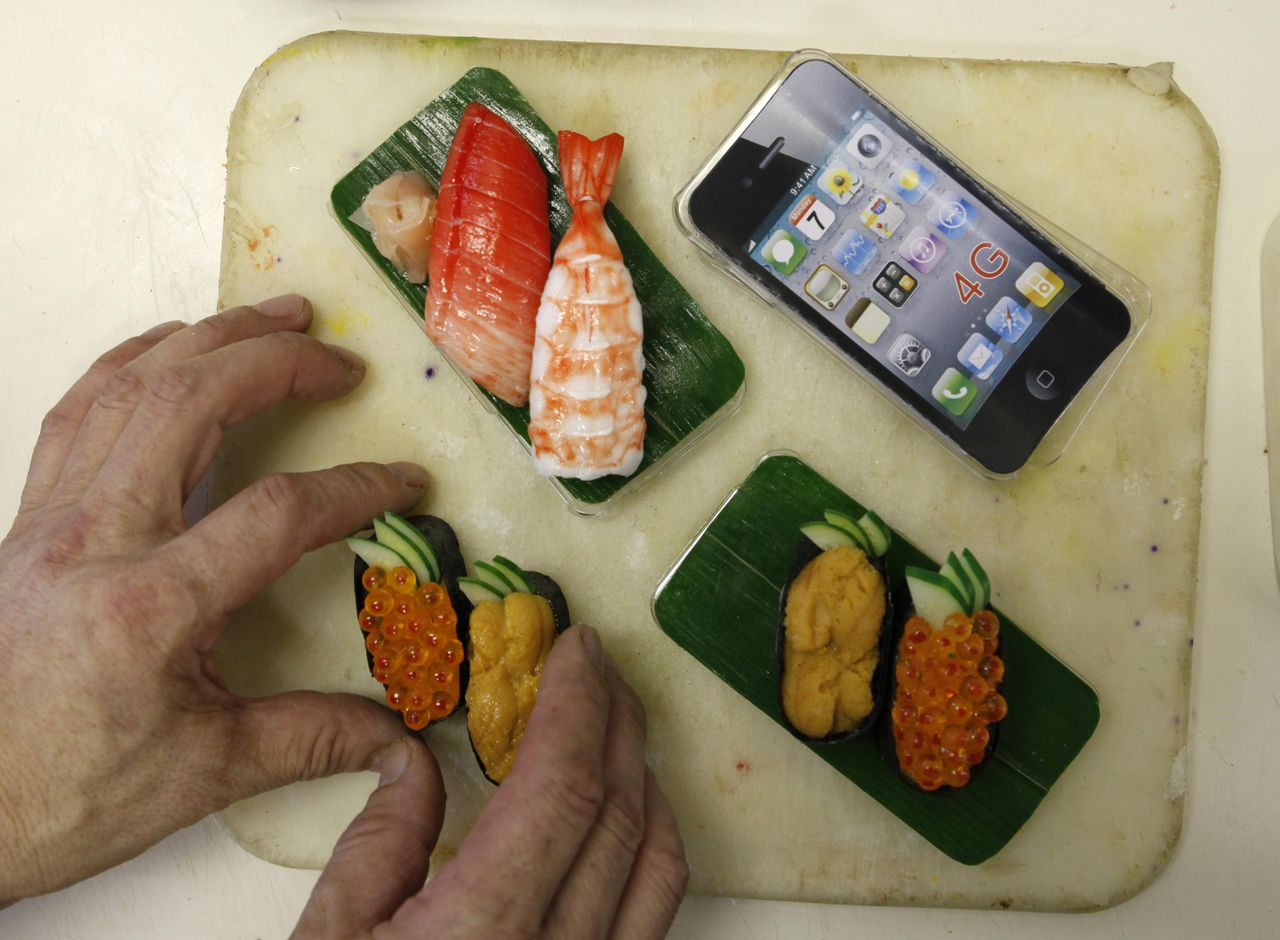 A worker makes an iPhone case decorated with plastic models of sushi at Suetake Sample, a plastic food model maker, in Yokohama, near Tokyo July 29, 2011. The company began producing iPhone cases decorated with plastic food models such as sushi and eel bowl since the end of last year. The prices of the handmade products vary from 2,000 - 4,000 yen ($26 - $56) in domestic and oversee markets. REUTERS/Kim Kyung-Hoon (JAPAN - Tags: SOCIETY FOOD ODDLY SCI TECH)