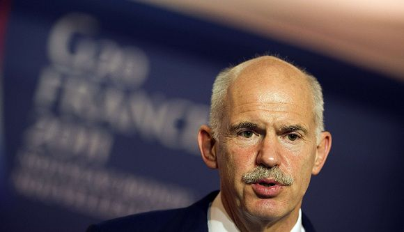 """Caption: Greek Prime Minister George Papandreou talks during a press conference following crisis talks with France's President, Germany's Chancellor, senior EU leaders and IMF director in Cannes, southeastern France, on November 2, 2011 on the eve of the G20 Summit of Heads of State and Government. Greece Prime Minister George Papandreou has said that a referendum on the European debt crisis deal for his country could be held as early as December 4 or 5, French President Nicolas Sarkozy said on November 2. The Greek leader said the popular vote could be held in a month's time after EU leaders including German Chancellor Angela Merkel told Papandreou during an emergency meeting that the referendum has to be held """"as soon as possible."""" AFP PHOTO / LIONEL BONAVENTURE"""